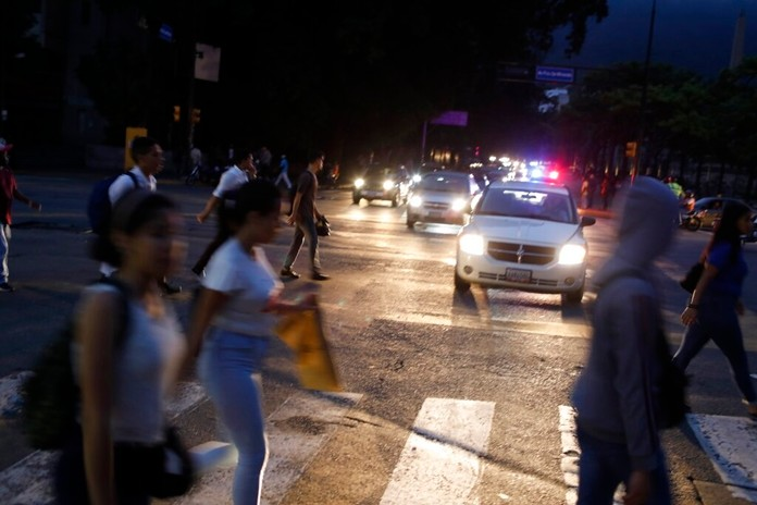 People cross a street during a blackout in Caracas, Venezuela, Monday, July 22, 2019. (AP Photo/Ariana Cubillos)