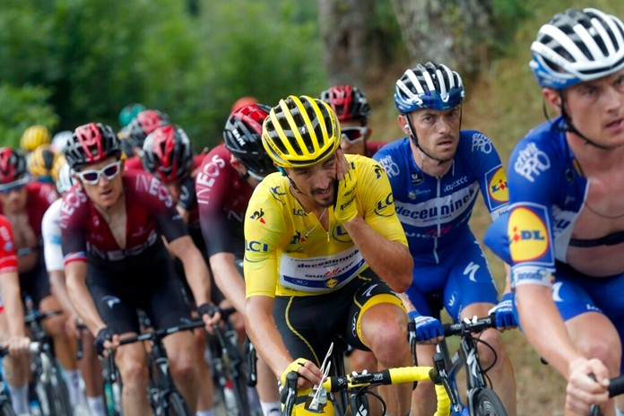 France's Julian Alaphilippe wearing the overall leader's yellow jersey rides in the pack with Britain's Geraint Thomas, left, during the fifteenth stage of the Tour de France cycling race, Sunday, July 21, 2019. (AP Photo/Thibault Camus)
