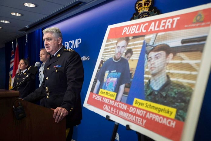 Security camera images recorded in Saskatchewan of Kam McLeod, 19, and Bryer Schmegelsky, 18, are displayed as Royal Canadian Mounted Police Assistant Commissioner Kevin Hackett speaks during a news conference in Surrey, British Columbia, on Tuesday, July 23, 2019. (Darryl Dyck/The Canadian Press via AP)