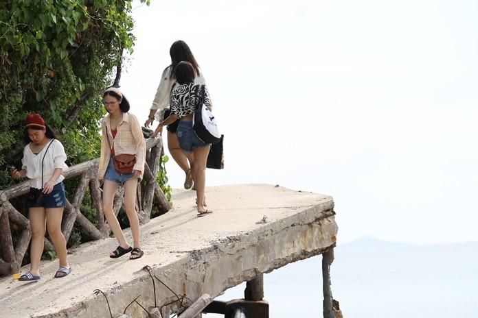 Tourists walk over the dilapidated pedestrian bridge at Koh Larn's Tien Beach.