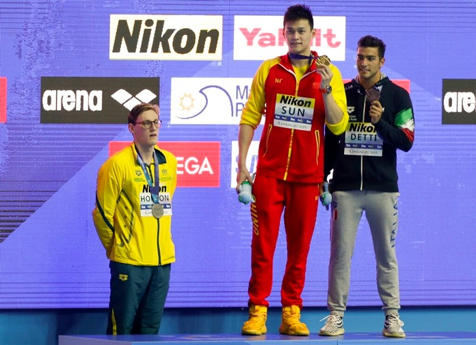 China's Sun Yang, centre, holds up his gold medal as silver medalist Australia's Mack Horton, left, stands away from the podium after the men's 400m freestyle final at the World Swimming Championships in Gwangju, South Korea, Sunday, July 21, 2019. (AP Photo/Mark Schiefelbein)