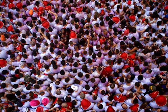 Revellers celebrate while waiting for the launch of the 'Chupinazo' rocket, to celebrate the official opening of the 2019 San Fermin fiestas with daily bull runs, bullfights, music and dancing in Pamplona, Spain, Saturday July 6, 2019. (AP Photo/Alvaro Barrientos)