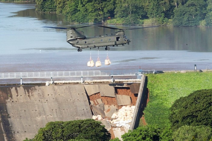 An RAF Chinook helicopter carrying sandbags arrives at the dam at Toddbrook reservoir near the village of Whaley Bridge, central England, Friday Aug. 2, 2019, after it was damaged by heavy rainfall. (Danny Lawson/PA via AP)