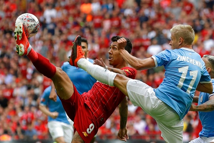 Liverpool's Roberto Firmino challenges for the ball with Manchester City's Oleksandr Zinchenko during the English Community Shield soccer match between Liverpool and Manchester City at Wembley stadium in London, Sunday, Aug. 4, 2019. (AP Photo/Kirsty Wigglesworth)
