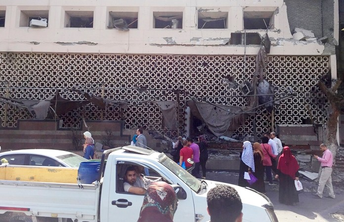 People survey the aftermath of a fiery car crash outside the National Cancer Institute in Cairo, Egypt, Monday, Aug. 5, 2019. (AP Photo/Maya Alleruzzo)