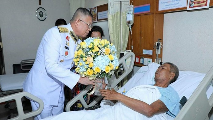 His Majesty the King's representative, Air Marshal Pakdee Saeng-xuto, presents flowers to one of the victims of the Bangkok bomb attack, Monday, August 5.