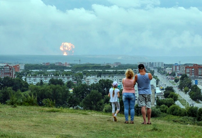 In this photo taken on Monday, Aug. 5, 2019, a family watches explosions at a military ammunition depot near the city of Achinsk in eastern Siberia's Krasnoyarsk region, in Achinsk, Russia. (AP Photo/Dmitry Dub)