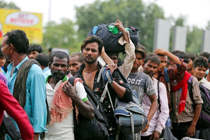 Indian migrant laborers carry their luggage and prepare to leave the region, at a railway station in Jammu, India, Wednesday, Aug. 7, 2019. (AP Photo/Channi Anand)