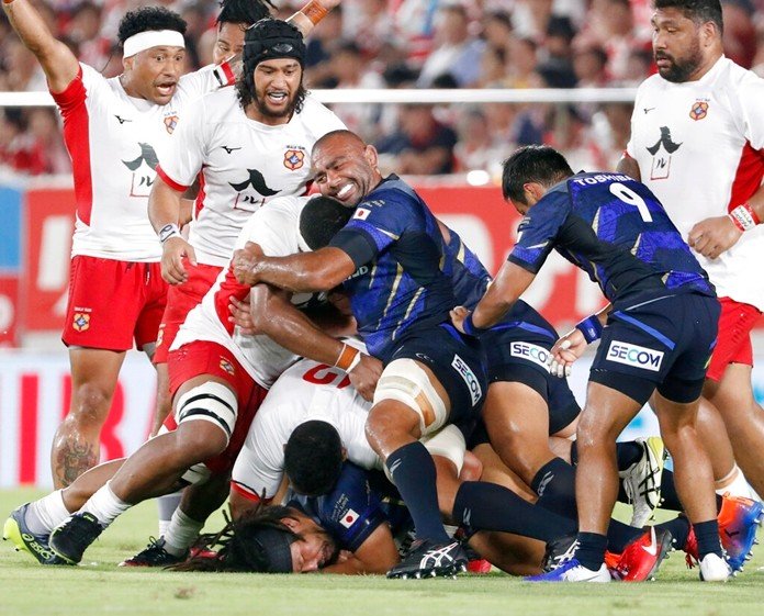 Japan's Michael Leitch, center, pushes with teammates against Tonga during a Pacific Nations Cup rugby match in Osaka, western Japan, Saturday, Aug. 3, 2019. (Kyodo News via AP)