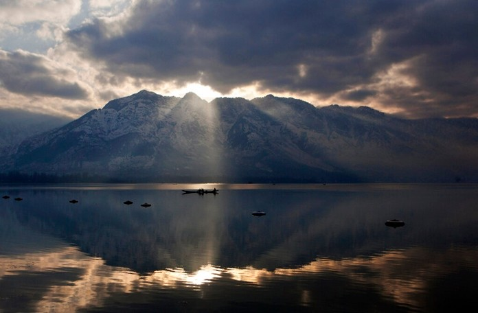 In this March 10, 2015 file photo, the sun peeks through a gap between clouds and a mountain as Kashmiri fishermen row their boats on their way home after working in Dal Lake in Srinagar, in Indian-controlled Kashmir. Kashmir's pristine Alpine landscape, ski resorts, lake houseboat stays and uninterrupted acres of apple orchards have long made it a global tourist draw. (AP Photo/Dar Yasin, File)