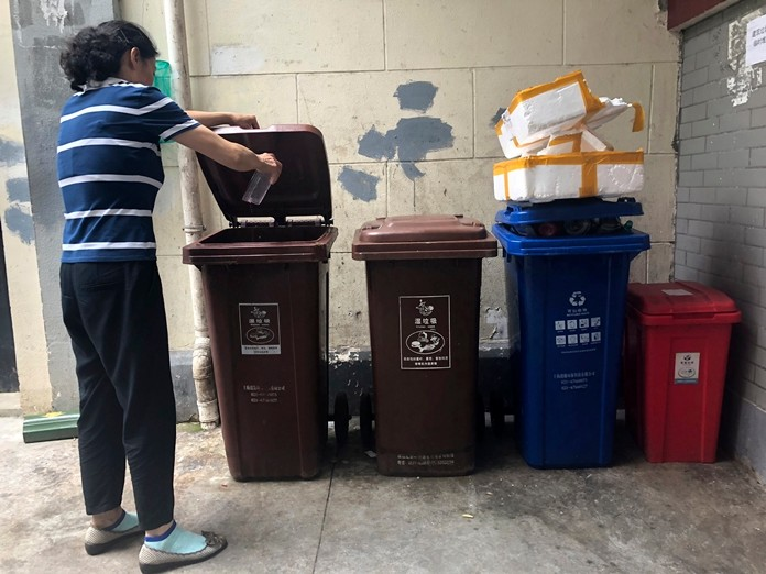 A resident pours kitchen wash in a garbage container marked for wet garbage in a residential community in Shanghai. (AP Photo/Chen Si)