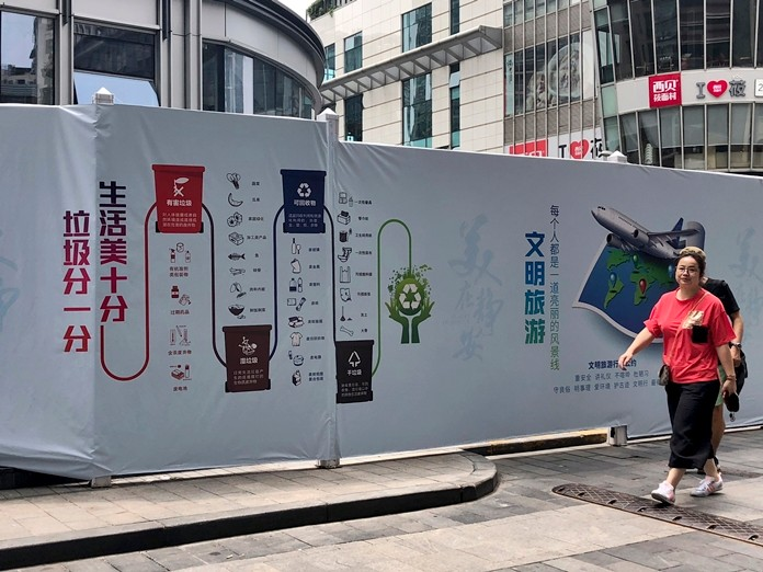 A woman walks past a publicity board highlighting waste separation and recycling regulations in downtown Shanghai, China. (AP Photo/Chen Si)