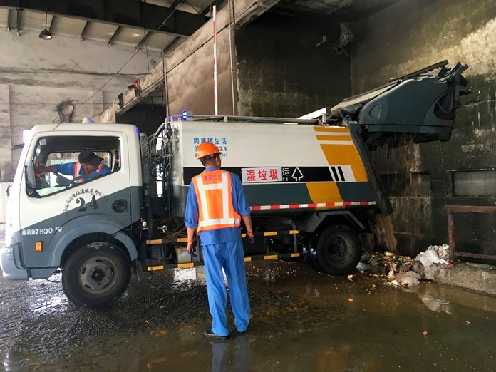 A trash collection truck deposits its load of wet garbage at a trash station in Shanghai. (AP Photo/Fu Ting)
