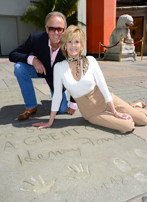 Jane Fonda, right, poses with her brother Peter Fonda in front of their father Henry Fonda's hand and footprints as the TCM Classic Film Festival honors Jane Fonda with a hand and footprint ceremony at the TCL Chinese Theatre in Los Angeles April 27, 2013. (Photo by Jordan Strauss/Invision/AP, File)