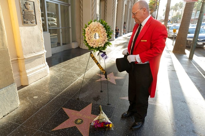 Unofficial Hollywood ambassador Gregg Donovan sets flowers on the Walk of Fame star of Peter Fonda in Los Angeles Friday, Aug. 16, 2019. (AP Photo/Damian Dovarganes)
