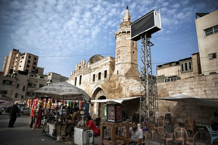 Palestinian vendors set up in front of the remains of the 13 century Barquq Castle, built by an Mamluk Sultan, in Khan Younis, Southern Gaza Strip Wednesday July 17, 2019. (AP Photo/Khalil Hamra)
