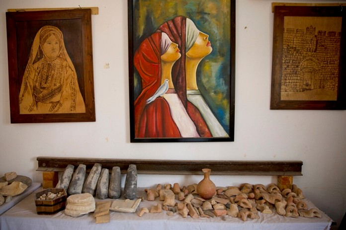 Paintings decorate the wall over ancient artifacts displayed inside Al-Qarara private museum in town of Khan Younis, Southern Gaza Strip July 17, 2019. (AP Photo/Khalil Hamra)
