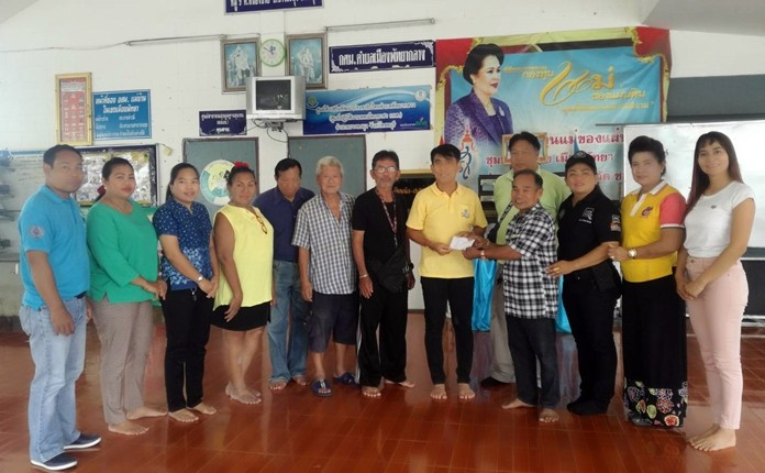 Lumduan Chimplee presents 10,000 baht to Jirawat Plukjai, Chairman of Chumsai Community for home repairs.