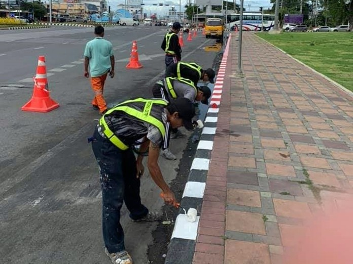 Workers paint red and white stripes on the curb which means, 'Strictly No Parking' at all times.