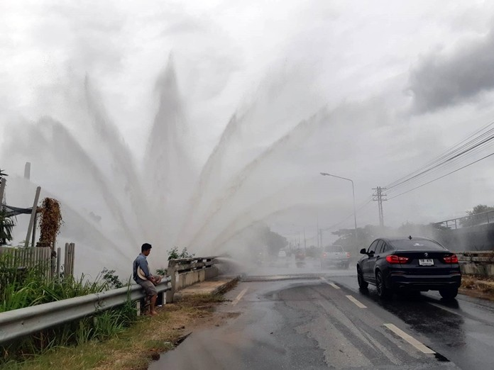 A local resident seems to be enjoying the 3-meter-high water fountain caused by a leaking large steel waterpipe along the railway road.