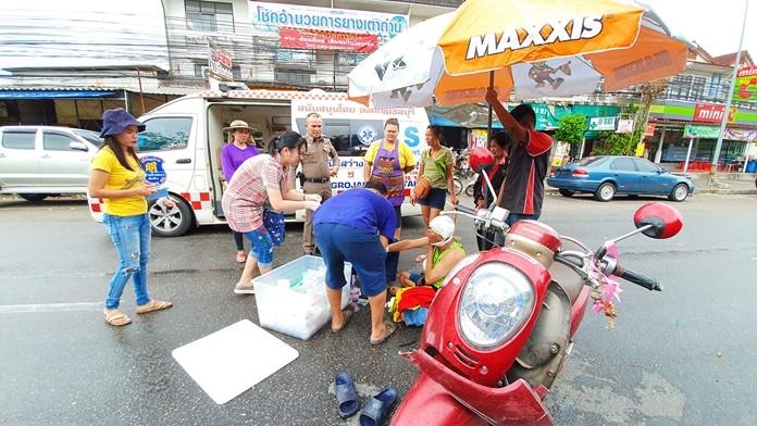 Pol. Maj. Somjit Sittibun and other good Samaritans assist the accident victim until the medical team arrived.