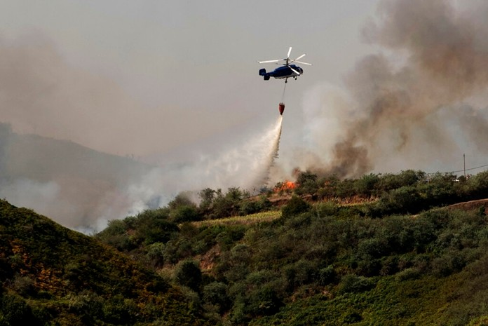 A helicopter operates over a wildfire in Canary Islands, Spain, Monday, Aug. 19, 2019. (AP Photo/Arturo Jimenez)