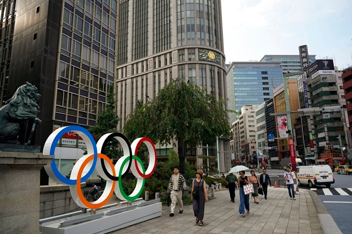 In this Monday, Aug. 19, 2019, photo, people walk past the Olympic rings in Tokyo. Tokyo is shaping up as a very pricey Olympics. Ticket demand is unprecedented, so scalping is sure to flourish. Hotel rates are soaring to five-six times normal. And getting here will be costly, particularly for fans from the Americas and Europe. (AP Photo/Jae C. Hong)