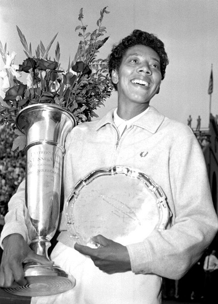 In this Sept. 9, 1957, file photo, Althea Gibson smiles as she holds her trophies she won by capturing the National women's singles tennis championship at the West Side Tennis Club in Forest Hills, N.Y. Gibson won an amazing 11 Grand Slam titles in three years from 1956-58, including the French Open, Wimbledon and U.S. Open. On Monday, Aug. 26, 2019, the USTA will unveil a statue in her honor at the U.S. Open. (AP Photo, File)