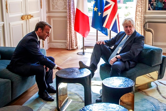 French President Emmanuel Macron, left, talks to Britain's Prime Minister Boris Johnson during their meeting at the Elysee Palace, Thursday, Aug. 22, 2019 in Paris. (Christophe Petit Tesson, Pool via AP)