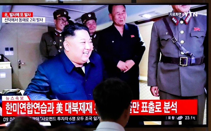 People watch a TV news program reporting North Korea's firing of projectiles with a file image of North Korean leader Kim Jong Un at the Seoul Railway Station in Seoul, South Korea, Saturday, Aug. 24, 2019. (AP Photo/Lee Jin-man)