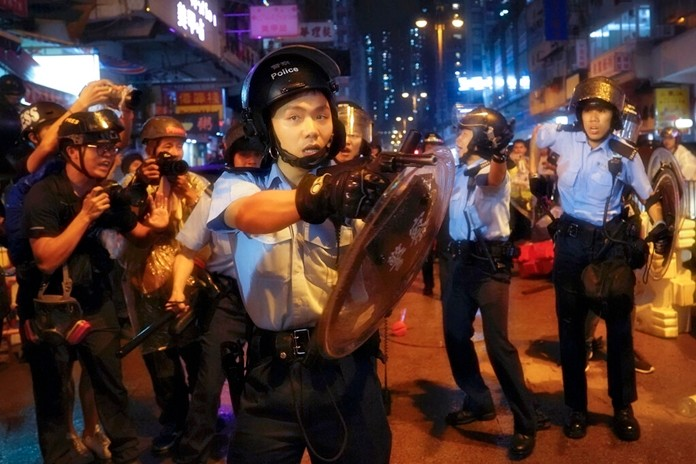 Policemen pull out their guns after a confrontation with demonstrators during a protest in Hong Kong, Sunday, Aug. 25, 2019. (AP Photo/Vincent Yu)