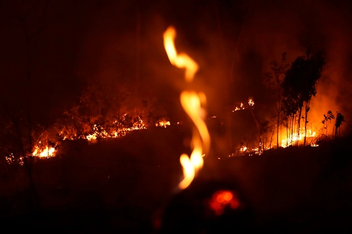 A fire burns in highway margins in the city of Porto Velho, Rondonia state, part of Brazil's Amazon, Sunday, Aug. 25, 2019. (AP Photo/Eraldo Peres)