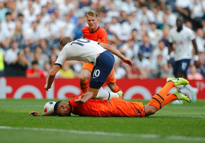 Tottenham's Harry Kane falls after he was tackled by Newcastle's Jamaal Lascelles during the English Premier League soccer match between Tottenham Hotspur and Newcastle United at Tottenham Hotspur Stadium in London, Sunday, Aug. 25, 2019. (AP Photo/Frank Augstein)