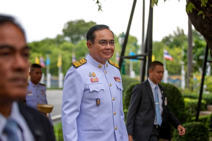 Prime Minister Prayuth Chan-ocha, center, surrounded by bodyguards, walks to attend a cabinet meeting at the Government House of Thailand in Bangkok, Tuesday, Aug. 27, 2019. (AP Photo/Gemunu Amarasinghe)