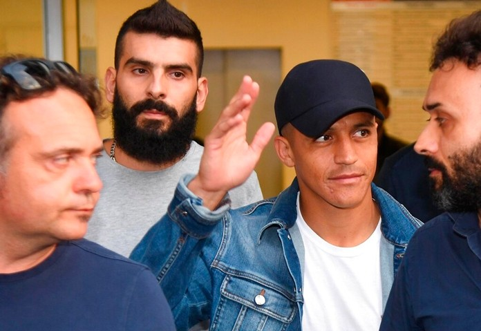 Alexis Sanchez, second from right, waves to fans upon his arrival at the Coni (Italian Olympic Committee) office for medical checks, in Milan, Italy, Wednesday, Aug. 28, 2019. Sanchez will leave Manchester united on a loan deal with the Italian Serie A soccer team, Inter Milan, Italian news agency ANSA said. (Daniel Dal Zennaro/ANSA via AP)