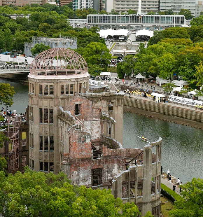 A ceremony to mark the 74th anniversary of the atomic bombing is held, in the background, as the Atomic Bomb Dome is seen in front at the Hiroshima Peace Memorial Park in Hiroshima, western Japan Tuesday, Aug. 6, 2019. (Kyodo News via AP)