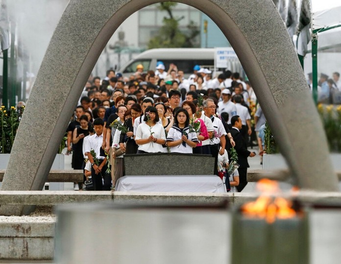 People pray for the atomic bomb victims in front of the cenotaph at the Hiroshima Peace Memorial Park in Hiroshima, western Japan during a ceremony to mark the 74th anniversary of the bombing Tuesday, Aug. 6, 2019. (Kyodo News via AP)