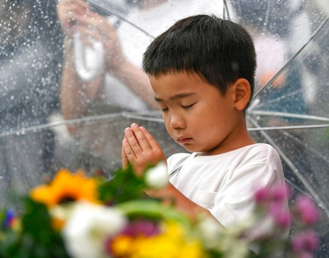 A boy prays for the atomic bomb victims in front of the cenotaph at the Hiroshima Peace Memorial Park in Hiroshima, western Japan during a ceremony to mark the 74th anniversary of the bombing Tuesday, Aug. 6, 2019. (Kyodo News via AP)