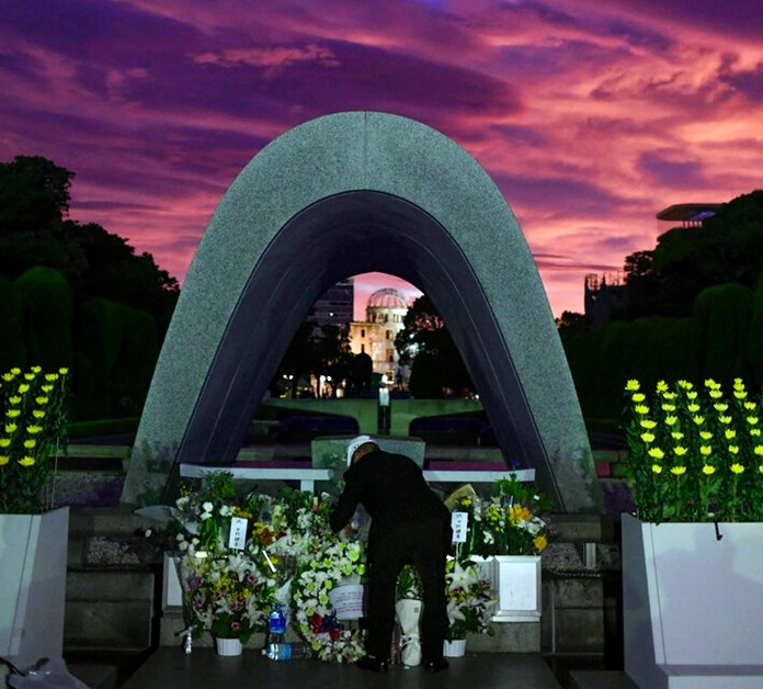 A man offers flowers for the atomic bomb victims in front of the cenotaph at the Hiroshima Peace Memorial Park in Hiroshima, western Japan during a ceremony to mark the 74th anniversary of the bombing early Tuesday, Aug. 6, 2019. (Kyodo News via AP)