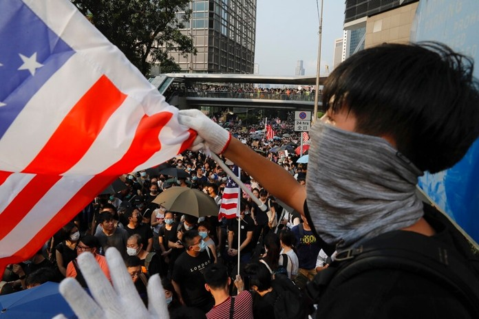 A protester waves a U.S. flag in Hong Kong, Sunday, Sept. 8, 2019. (AP Photo/Kin Cheung)