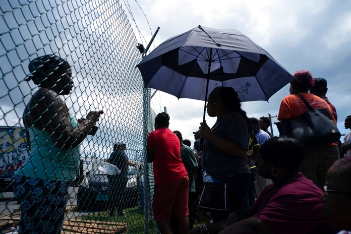People gather at the port for aid sent by family members and friends in the aftermath of Hurricane Dorian in Freeport, Bahamas, Tuesday, Sept. 10, 2019. (AP Photo/Ramon Espinosa)