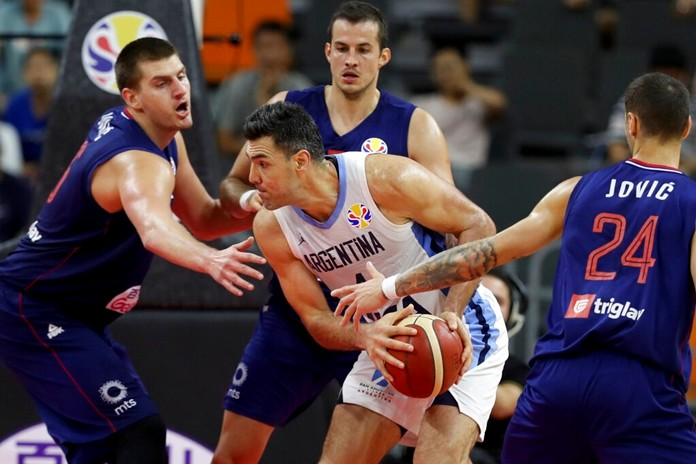 Argentina's Luis Scola tries to get past Serbian defenders during a quarterfinal match for the FIBA Basketball World Cup in Dongguan in southern China's Guangdong province on Tuesday, Sept. 10, 2019. (AP Photo/Ng Han Guan)