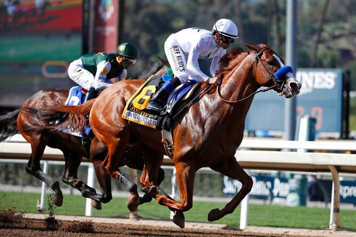 In this April 7, 2018, file photo, Justify, ridden by Mike Smith, gallops past Bolt d'Oro, left, with jockey Javier Castellano, during the Santa Anita Derby horse race at Santa Anita in Arcadia, Calif. (AP Photo/Jae C. Hong)