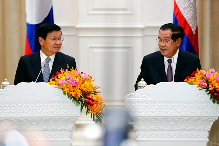 Cambodian Prime Minister Hun Sen, right, talks with his Laos counterpart Thonloun Sisoulith during a press conference, in Phnom Penh, Cambodia, Thursday, Sept. 12, 2019. (AP Photo/Heng Sinith)