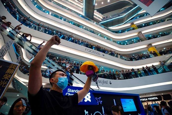 """Demonstrators sing a theme song written by protestors """"Glory to Hong Kong"""" at the Times Square shopping mall in Hong Kong, Thursday, Sept. 12, 2019. (AP Photo/Vincent Yu)"""