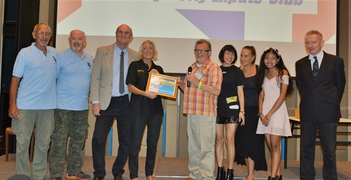"""MC Bob Smith presents Pattaya Players' Wendy Kahn, who directed the performance of """"The Allotment Plot,"""" with the PCEC's Certificate of Appreciation while the Players look on."""