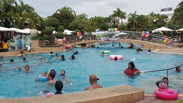 Employees and their families take turns jumping, swimming and having a great time in the swimming pool.
