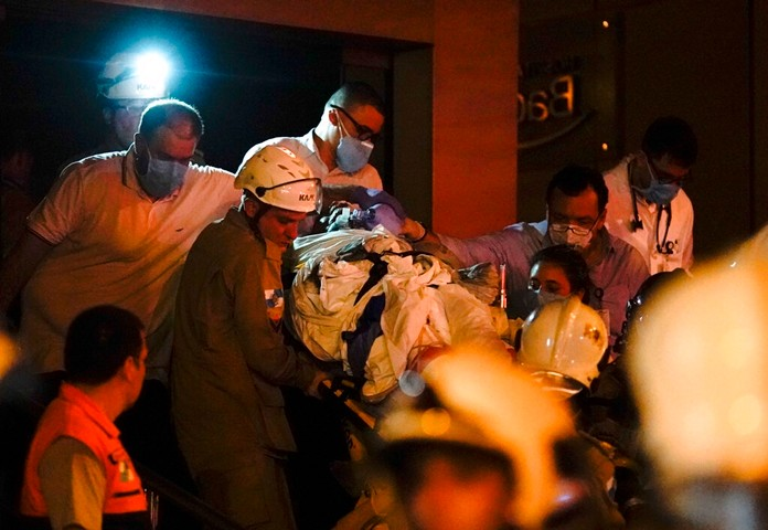 A patient is evacuated from a burning hospital in Rio de Janeiro, Brazil, Thursday, Sept. 12, 2019. (AP Photo/Leo Correa)