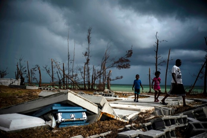 People walk next to a shattered and water-filled coffin in the aftermath of Hurricane Dorian, at the cemetery in Mclean's Town, Grand Bahama, Bahamas, Friday Sept. 13, 2019. (AP Photo/Ramon Espinosa)