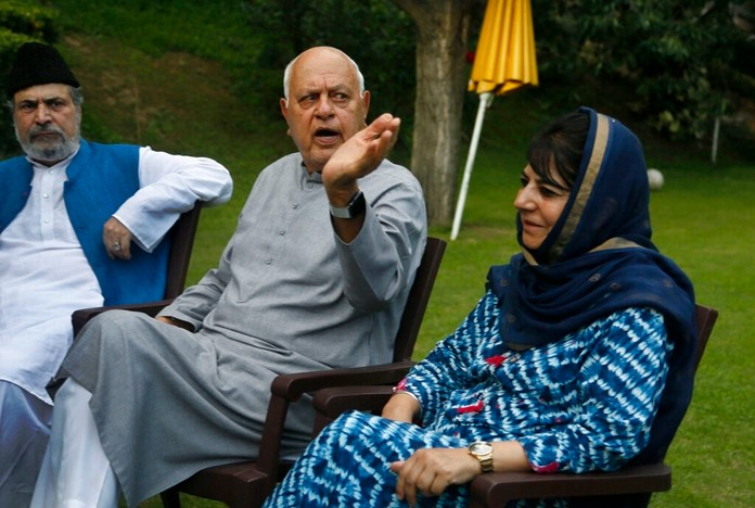 In this Aug. 4, 2019, file photo, National Conference president Farooq Abdullah, center, gestures during an all parties meeting in Srinagar, Indian controlled Kashmir. (AP Photo/Mukhtar Khan)